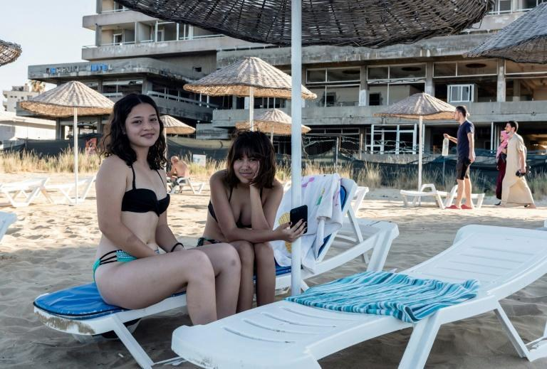 Tourists pose for a picture in the fenced-off area of Varosha in Famagusta town in the self-proclaimed Turkish Republic of Northern Cyprus in June 2021