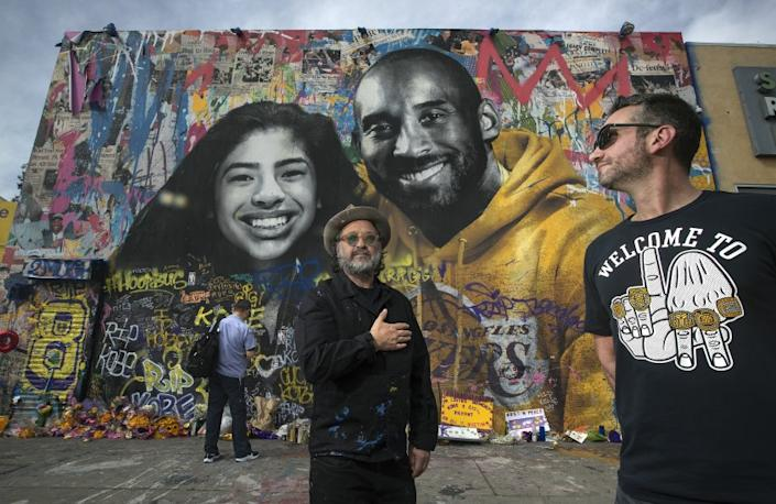 "Artist Thierry ""Mr. Brainwash"" Guetta, left, and Mike Asner, creator of the KobeMural website and Instagram account, stand in front of the mural Guetta created of Kobe Bryant and his daughter Gianna five days after they died. The photo was taken on Feb. 27; a month later, heavy rains destroyed the paper and paste tribute on Guetta's building in the 1200 block of South La Brea Avenue in Mid-Wilshire. <span class=""copyright"">(Los Angeles Times)</span>"