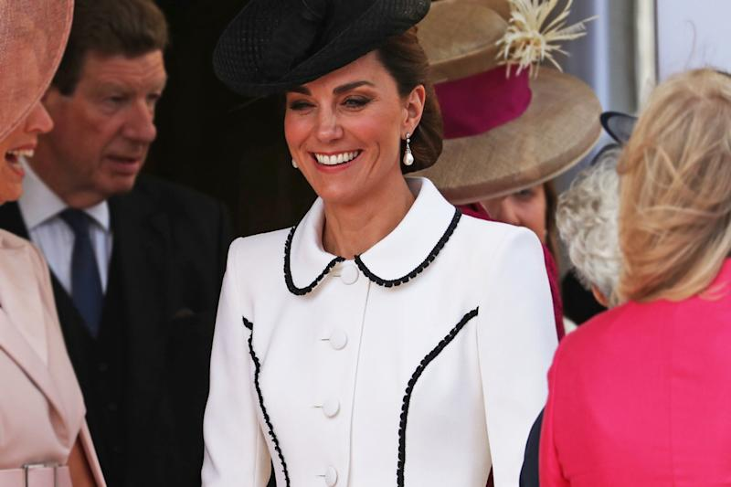 """Kate Middleton stepped out with members of the British royal family on Monday afternoon for the Order of the Garter ceremony.The annual event, which celebrates the most senior order of the chivalry in the UK, took place at St George's Chapel in Windsor, and was also attended by The Queen, Prince William and Prince Charles.For the occasion, the duchess cut a chic figure in a perfectly tailored white coat dress with black trim by Catherine Walker, a British label often favoured by the duchess, which was also a go-to designer for her late mother-in-law, Princess Diana.The 'Liza' coat featured a flattering peplum silhouette and is described on the website as: """"A contemporary take on a '50's look, this coatdress in ivory wool crepe has copped jacket 'panels' edged in fine black lace.""""Kate accessorised the look with contrasting black accessories, including a Lock & Co hat, clutch bag and classic black court shoes with subtle cut-out detail. The duchess finished off the look with a pair of pearl drop earrings by Collingwood jewellers, which belonged to Princess Diana."""