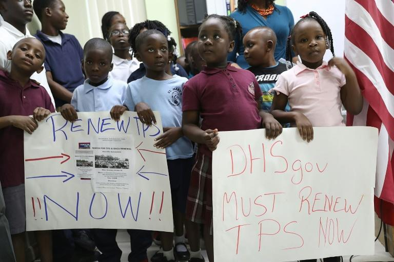 Children hold posters asking the US government to renew Temporary Protected Status during a press conference at the office of the Haitian Women of Miami on November 6, 2017