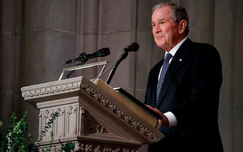 Former President George W Bush pauses as speaks  - Credit: AFP
