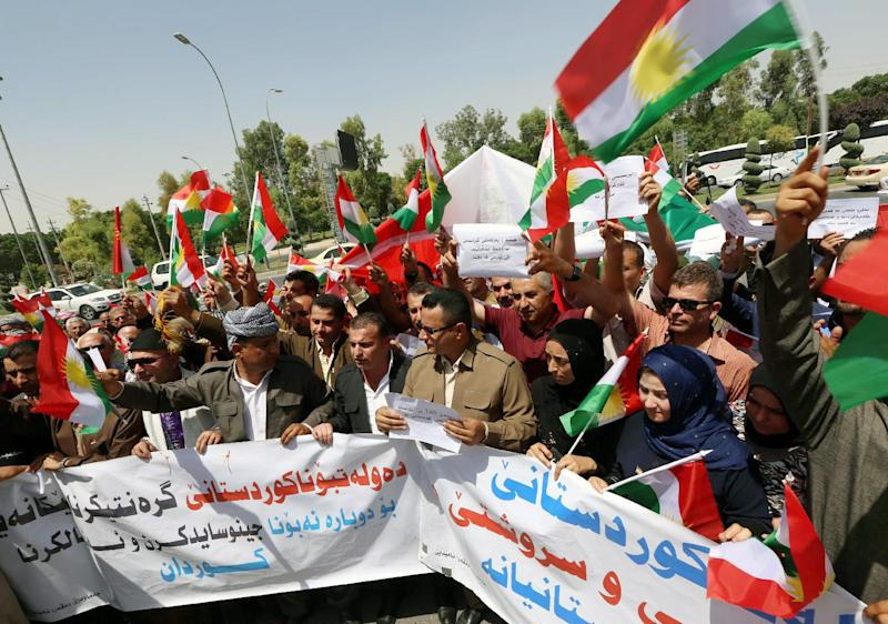 Iraqi Kurdish protesters hold a banner and wave flags of their autonomous Kurdistan region during a demonstration to claim for its independence on July 3, 2014 outside the Kurdistan parliament building in Arbil, in northern Iraq (AFP Photo/Safin Hamed)