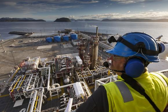 A man looking down over an oil and gas processing plant.
