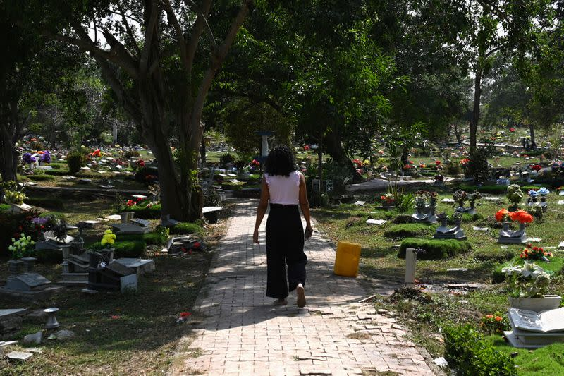 Claudia Patricia Fortich, widow of late oil tanker captain Jaime Herrera Orozco, who was murdered on his ship while anchored off Venezuela, walks in the middle of a graveyard, in Cartagena