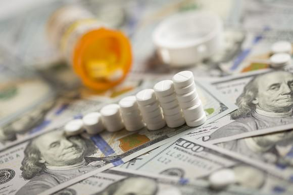 An ascending stack of prescription tablets lying atop a messy pile of hundred dollar bills.