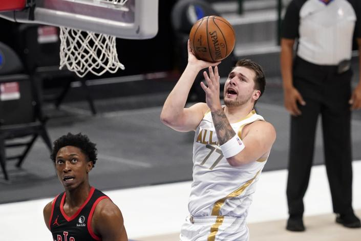 Toronto Raptors' Stanley Johnson (5) looks on as Dallas Mavericks guard Luka Doncic (77) takes a shot in the first half of an NBA basketball game in Dallas, Friday, May 14, 2021. (AP Photo/Tony Gutierrez)