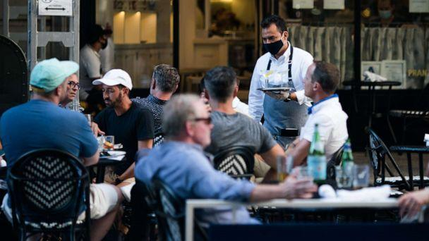 PHOTO: A waiter wearing a protective mask serves drinks outside a restaurant on July 21, 2020, in New York. (Jeenah Moon/Getty Images)