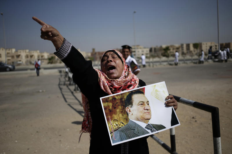 An Egyptian woman carrying a photo of ousted president Hosni Mubarak chants slogans against ousted President Mohammed Morsi and the Muslim Brotherhood as she expresses her support for Mubarak at a court in Cairo, Egypt, Saturday, Sept. 14, 2013. The ousted long-time autocrat went back in court as his trial resumed on charges related to the killings of some 900 protesters during the 2011 uprising that led to his ouster. (AP Photo/Hassan Ammar)