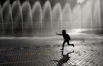 A child runs past a fountain in Yekaterinburg, Russia June 28, 2018. REUTERS/Darren Staples