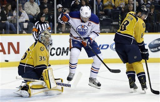 Edmonton Oilers center Shawn Horcoff (10) jumps out of the way of a shot by teammate Corey Potter, unseen, that gets by Nashville Predators goalie Pekka Rinne (35), of Finland, for a goal in the first period of an NHL hockey game on Monday, March 25, 2013, in Nashville, Tenn. Also defending for the Predators is Kevin Klein (8). (AP Photo/Mark Humphrey)
