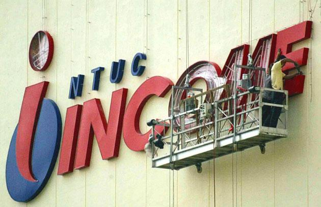 Workers install new sign display of National Trade Union Congress (NTUC) on its building in Singapore 17 January 2003. (AFP photo/Roslan Rahman)