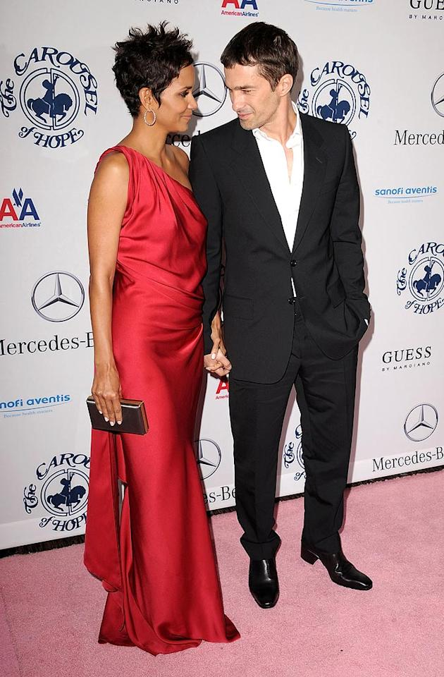 """Halle Berry and Olivier Martinez hit the red carpet together for their official public debut as a couple at the 32nd annual Carousel Of Hope Ball in Beverly Hills. Berry wowed the crowd in a stunning red YSL Pre-Fall 2010 gown, while her handsome French beau was suave in a well-cut suit and black boots. Steve Granitz/<a href=""""http://www.wireimage.com"""" target=""""new"""">WireImage.com</a> - October 23, 2010"""
