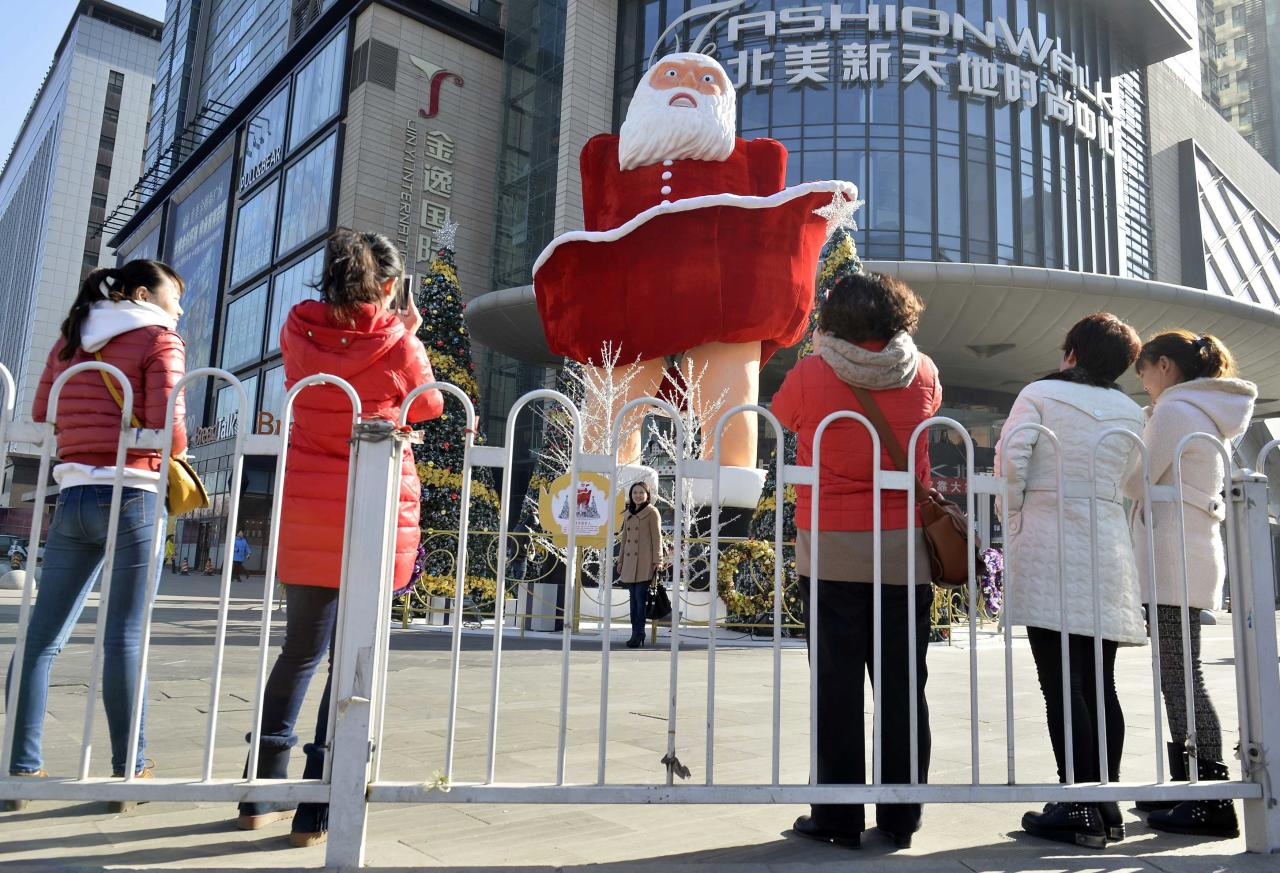 Women take pictures in front of a Santa Claus figure outside a shopping mall ahead of Christmas in Taiyuan, Shanxi province, December 11, 2013. REUTERS/Jon Woo (CHINA - Tags: SOCIETY) CHINA OUT. NO COMMERCIAL OR EDITORIAL SALES IN CHINA