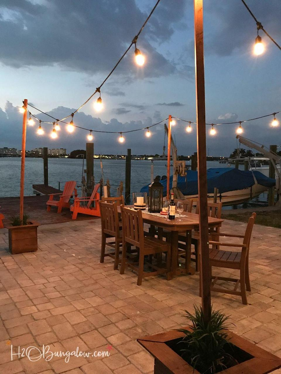 """<p>Whether you have an ocean- or river-side sitting area or simply a spacious backyard sans water, hanging simple string lights can make a major impact. And, if you don't have trees to hang them from, you'll be glad this DIY teaches you how to craft poles. </p><p><strong>Get the tutorial at <a href=""""https://h2obungalow.com/diy-outdoor-string-lights-poles/"""" rel=""""nofollow noopener"""" target=""""_blank"""" data-ylk=""""slk:H2O Bungalow"""" class=""""link rapid-noclick-resp"""">H2O Bungalow</a>.</strong></p><p><a class=""""link rapid-noclick-resp"""" href=""""https://www.amazon.com/Outdoor-Commercial-Waterproof-Dimmable-Backyard/dp/B07HSYVD1M/?tag=syn-yahoo-20&ascsubtag=%5Bartid%7C10050.g.31137877%5Bsrc%7Cyahoo-us"""" rel=""""nofollow noopener"""" target=""""_blank"""" data-ylk=""""slk:SHOP STRING LIGHTS"""">SHOP STRING LIGHTS</a></p>"""