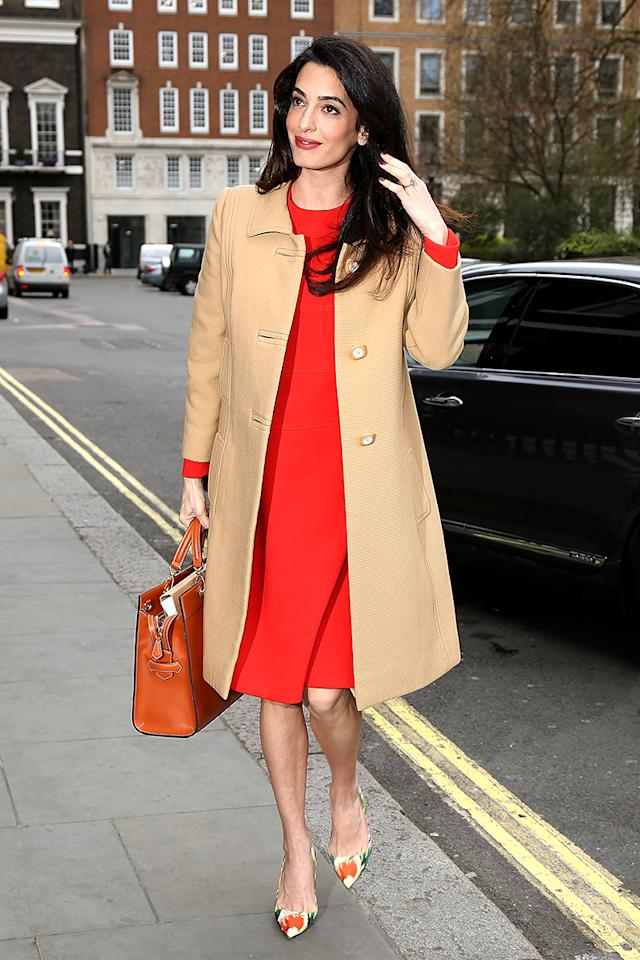 <p>Pregnancy looks good on Amal Clooney! The international human rights lawyer — who is expecting twins with George Clooney — was glowing even more than usual as she arrived at a gathering in London to deliver a speech on war crimes in Syria and Iraq while wearing a bright red vintage Dior dress, camel Balmain coat, and floral Oscar de la Renta slingbacks. (Photo: Neil Mockford/GC Images) </p>