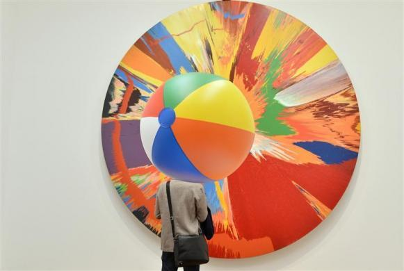 A visitor views a Spin Painting by British artist Damien Hirst at the Tate Modern gallery in London April 2, 2012. Hirst's retrospective show runs from April 4 to September 9.
