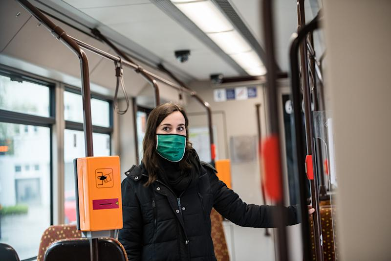 JENA, GERMANY - APRIL 03: Sophie Frick wears a protective face masks in a tram at a press meeting of the transport companie 'Jenaer Nahverkehr' on April 3, 2020 in Jena, Germany. A three-part city ordinance is going into effect requiring people to wear protective face masks under circumstances that include shopping, riding public transport and workplaces where social distancing is difficult. A face mask requirement is a current issue of controversy across Germany, with the federal government so far declining to make wearing one in public mandatory. Germany is struggling with a shortage of face masks, and the requirement in Jena also allows the use of scarves and other materials to shield one's face as a means to reduce the risk of anyone infected with Covid-19 from infecting others. (Photo by Jens Schlueter/Getty Images)