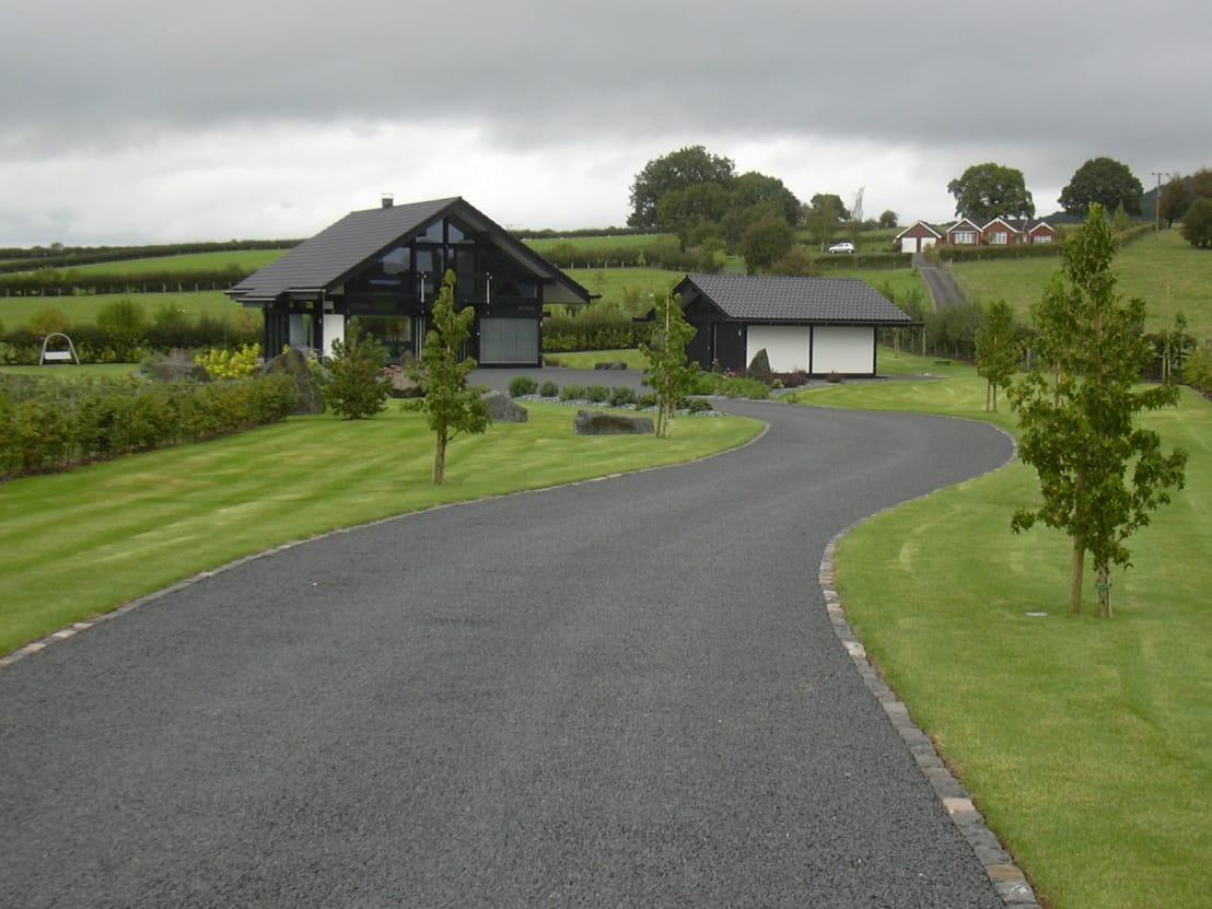 <p>In terms of driveway ideas, UK homes can have very specific needs, depending on location, but one material and finish is popular across the board and that's asphalt. Relatively cost effective, which is ideal for anyone investigating cheap driveway ideas, it is also simple to pour, level and maintain. </p><p>Asphalt might not sound very exotic or exciting, but given how dark the finish is, it always looks neat, ordered and deliberate, not to mention very sleek. Some stone edging will set the look off perfectly and add something of an organic flavour into the mix too.</p>  Credits: homify / Unique Landscapes