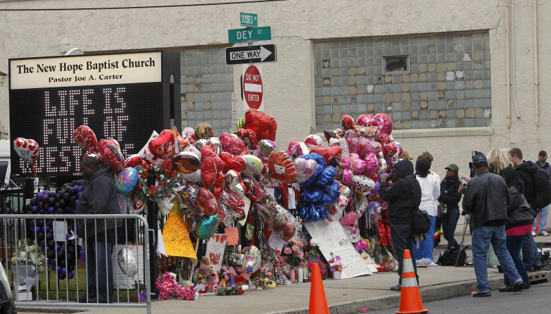 Fans and media surround a make-shift memorial as the pay their respects to Whitney Houston at New Hope Baptist Church, in Newark, N.J., Wednesday, Feb. 15, 2012. The 48-year-old pop star was found dead in the bathtub in her hotel room at the Beverly Hilton Hotel on Saturday, hours before she was supposed to appear at a pre-Grammy gala. Houston's funeral will be held at the church on Saturday. (AP Photo/Rich Schultz)