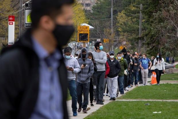 Residents of the Jane and Finch community, in northwest Toronto's M3N area code, form a long line outside a temporary COVID-19 vaccination clinic at the Driftwood Community Centre on Apr. 19, 2021. (Evan Mitsui/CBC - image credit)