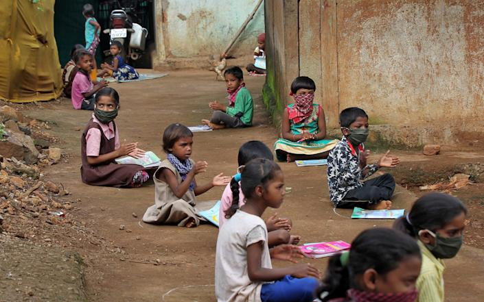 Children, who have missed their online classes due to a lack of internet facilities listen to pre-recorded lessons over loudspeakers in Dandwal village in the western state of Maharashtra, India - Reuters