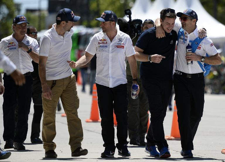 (L-R) Peugeot's driver Carlos Sainz of Spain, French former racing driver Luc Alphand, and Peugeot's French drivers Stephane Peterhansel and Cyril Despres are pictured during a technical check-up in Buenos Aires, on January 2, 2015
