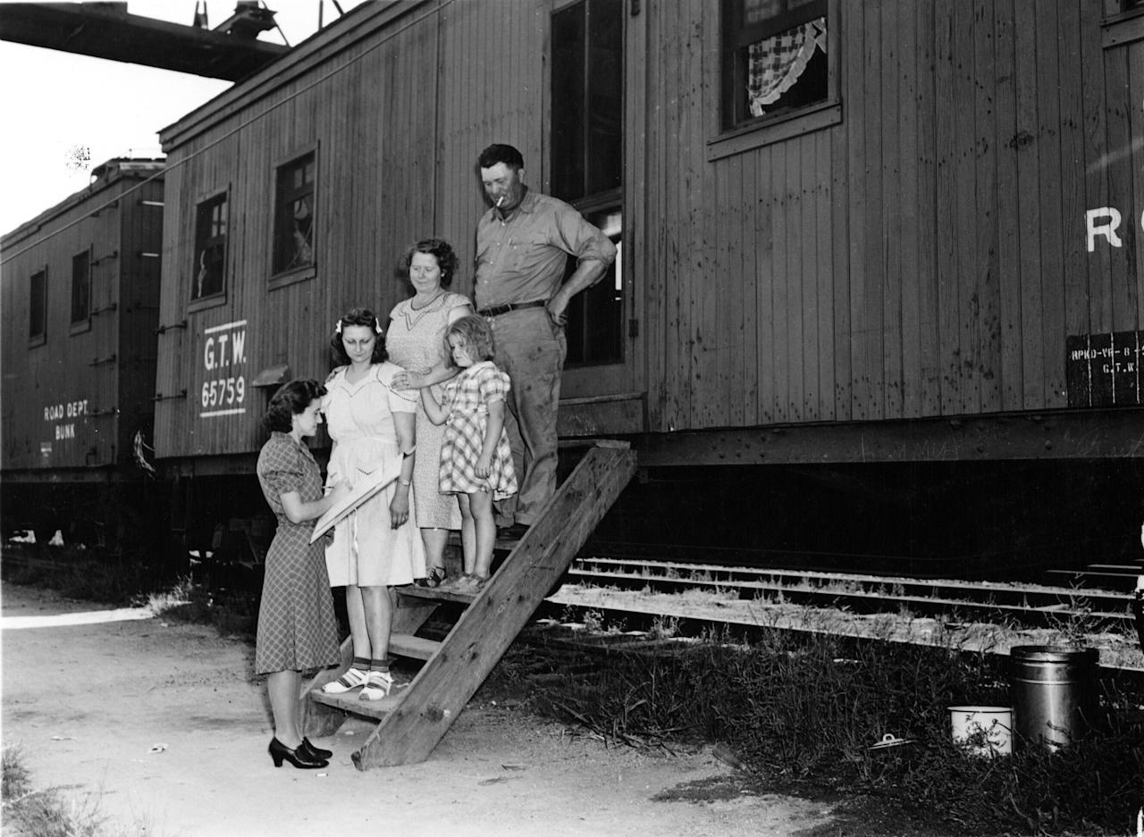 In this photo provided by the National Archives at College Park, an enumerator, left, interviews a family outside a rail car for the 1940 Census. Veiled in secrecy for 72 years because of privacy protections, the 1940 U.S. Census is the first historical federal decennial survey to be made available on the Internet initially rather than on microfilm. (AP Photo/National Archives at College Park)