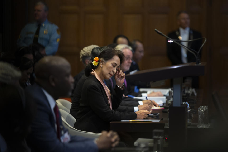 Myanmar's leader Aung San Suu Kyi, center, and Gambia's Justice Minister Aboubacarr Tambadou, left, listen to judges in the court room of the International Court of Justice for the first day of three days of hearings in The Hague, Netherlands, Tuesday, Dec. 10, 2019. Aung San Suu Kyi will represent Myanmar in a case filed by Gambia at the ICJ, the United Nations' highest court, accusing Myanmar of genocide in its campaign against the Rohingya Muslim minority. (AP Photo/Peter Dejong)