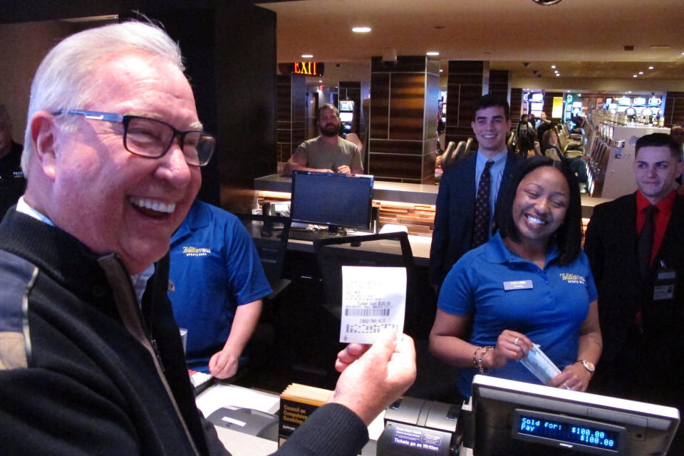 Former Philadelphia Eagles quarterback Ron Jaworski holds a ticket showing his $100 bet on the Philadelphia Phillies to win the 2019 World Series at the William Hill sportsbook in the Tropicana casino in Atlantic City N.J., March 8, 2019. Caesars Entertainment announced Wednesday, Sept. 30, 2020, it is buying William Hill for $3.7 billion. (AP Photo/Wayne Parry)