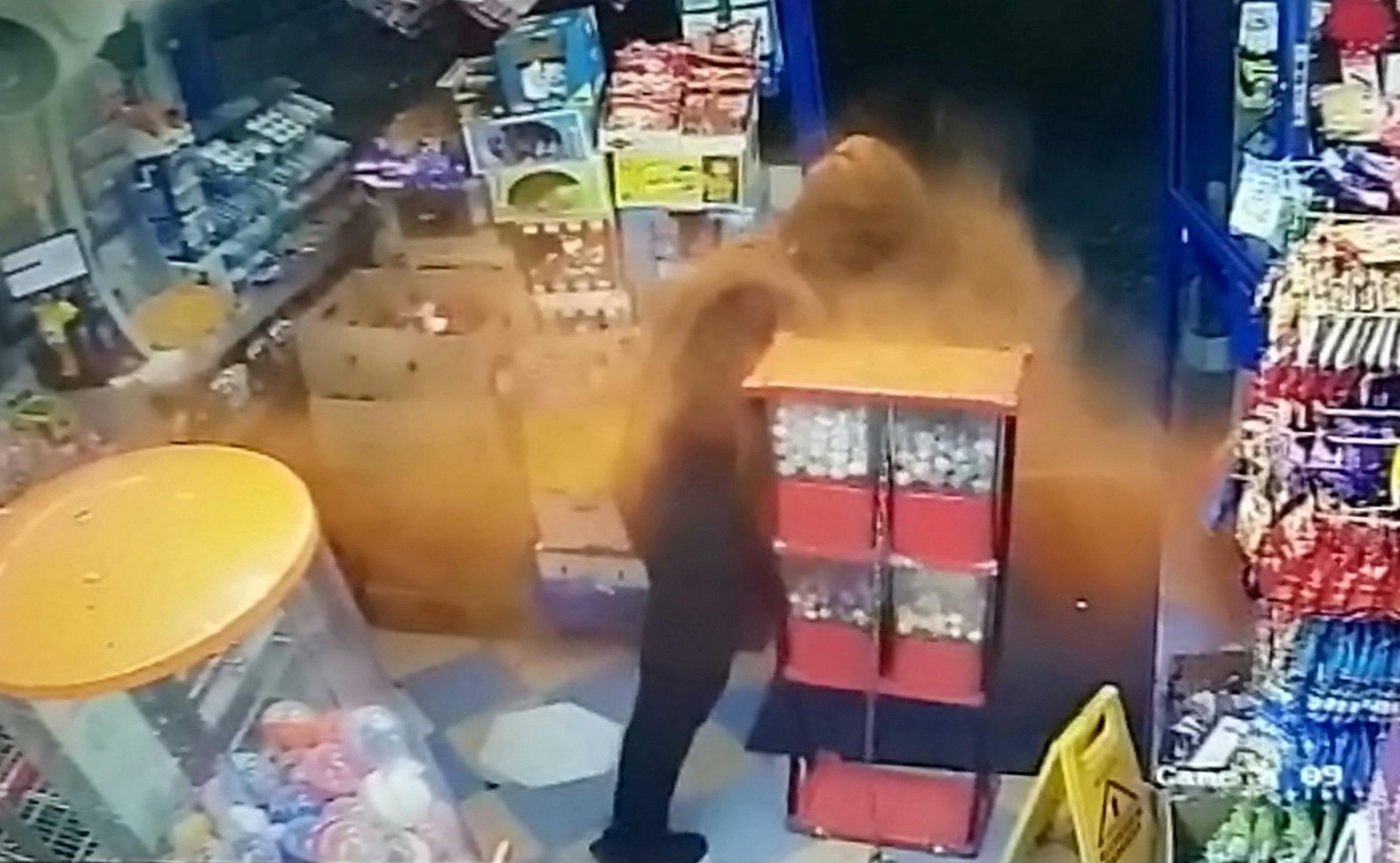 Watch this incredible moment where a brave shop owner lobs chilli powder at a thug (Picture: SWNS)