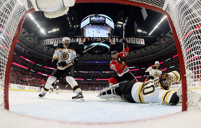 Boston Bruins goalie Tuukka Rask (40) makes a save on a shot by Chicago Blackhawks center Jonathan Toews (19) as Boston Bruins defenseman Zdeno Chara (33) watches during the second period of Game 1 in their NHL Stanley Cup Final hockey series, Wednesday, June 12, 2013, in Chicago. (AP Photo/Bruce Bennett, Pool)
