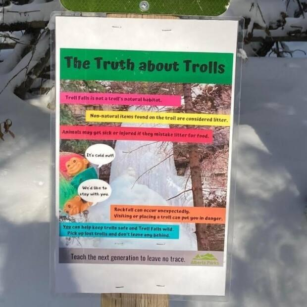'Troll Falls is not a troll's natural habitat,' explain the kid-friendly signs posted by Alberta Parks at the popular short hike in Kananaskis. Hundreds of the wild-haired plastic toys have been hidden in the area in the past few years by hikers. (Friends of Kananaskis Country Facebook page - image credit)