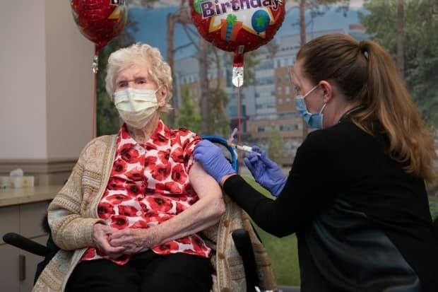 Phyllis Ridgway, left, receives a COVID-19 vaccinationon Saturday at Toronto's Sunnybrook Health Sciences Centre. At age 114, she is the oldest known living person in Canada. (Kevin Van Paassen/Sunnybrook Health Sciences Centre - image credit)