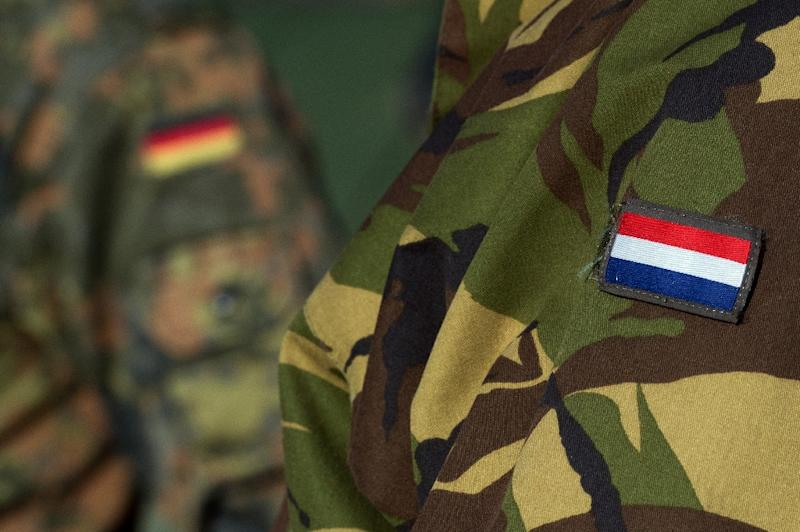 A Dutch (R) and a German soldier take part in a joint military exercise on February 9, 2016 at the Oberlausitz army training camp near Werdeck close to Weisswasser and the Polish border in eastern Germany