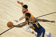 Phoenix Suns guard Devin Booker and Utah Jazz forward Royce O'Neale (23) battle for the ball during the first half of an NBA basketball game, Friday, April 30, 2021, in Phoenix. (AP Photo/Matt York)