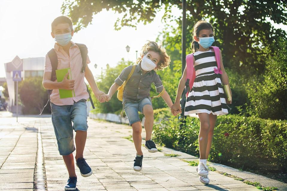 School during COVID- 19. Three happy children with backpacks wearing face protective masks. Coronavirus epidemic. New normal.