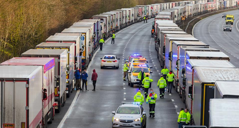 Police and emergency services distribute water and supplies to queues of stationary lorries on the M20 motorway between Ashford and Folkestone in Kent, Britain, December 23