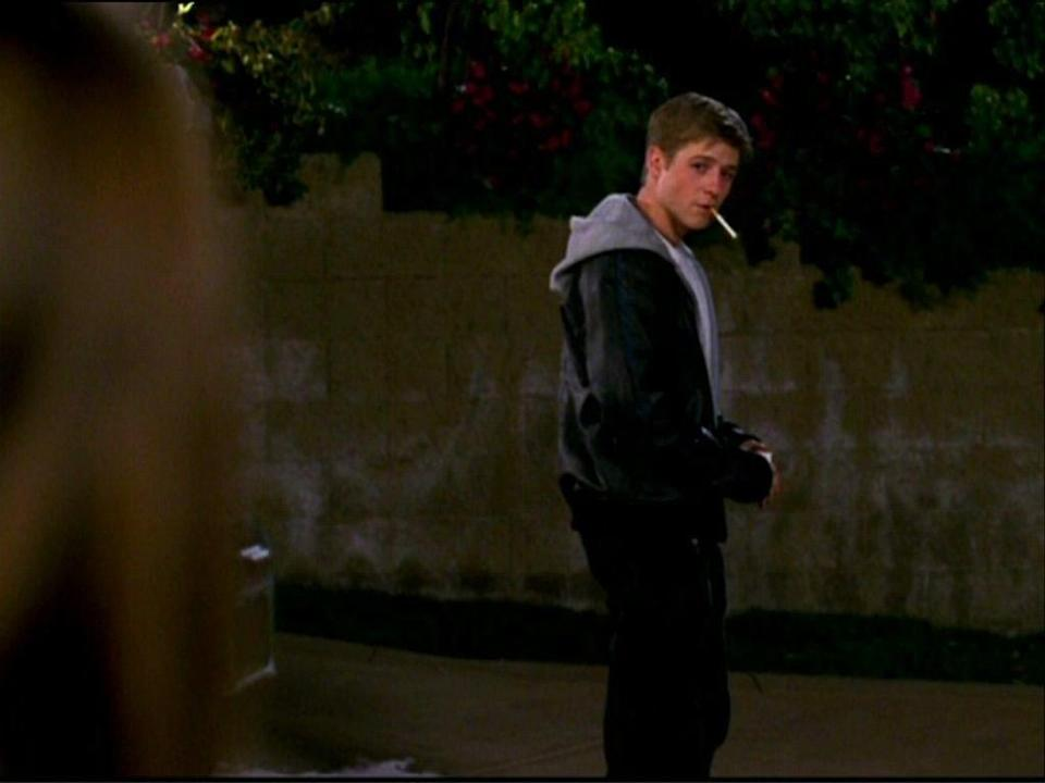 Ryan stands in a driveway with a cigarette in his mouth