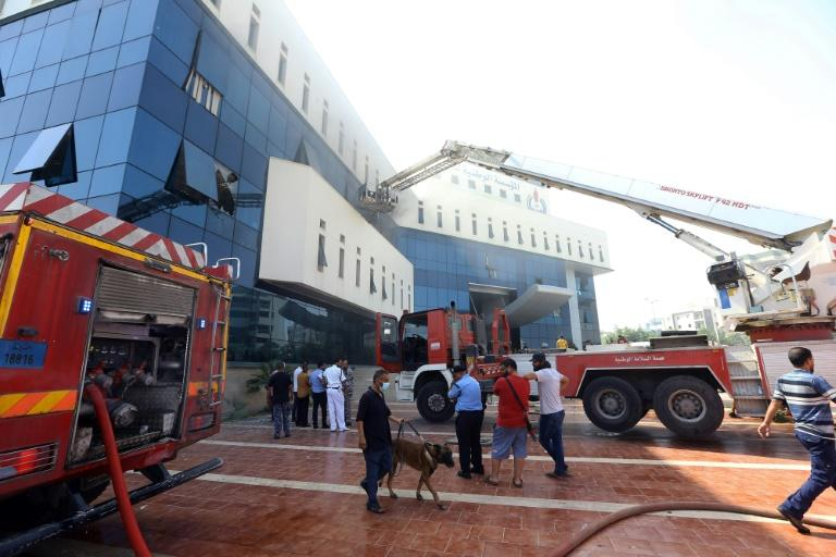 Firefighters and rescuers gather in front of the headquarters of Libya's National Oil Company in the capital Tripoli on September 10, 2018