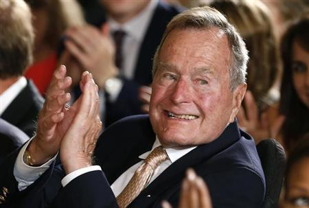 Former President George H. W. Bush applauds during an event to honor the winner of the 5,000th Daily Point of Light Award at the White House in Washington