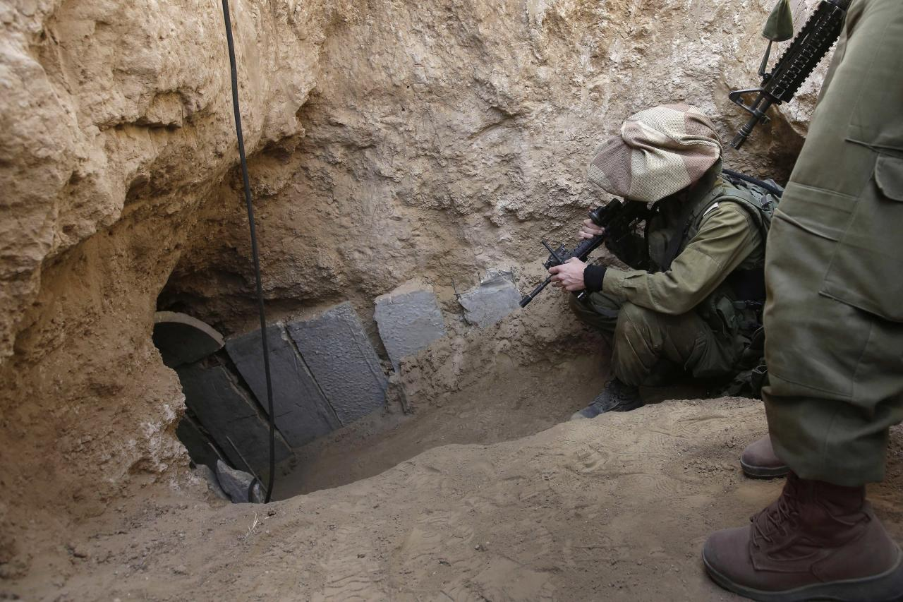 "FILE - In this Sunday, Oct. 13, 2013 file photo, Israeli soldiers enter a tunnel discovered near the Israel Gaza border. They've been dubbed ""lower Gaza,"" compared to the Underground, the Metro or the subway and depicted as a bone-chilling, strategic threat to Israel. Hamas' web of tunnels is taking center stage in the relentless conflict between the militant group and Israel, with Israel's ground offensive placing their destruction as a key objective. (AP Photo/Tsafrir Abayov, File)"