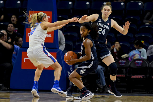 Connecticut guard Crystal Dangerfield, center, grabs a rebound away from DePaul guard Kelly Campbell, left, and guard Anna Makurat (24) during the second half of an NCAA college basketball game on Monday, Dec. 16, 2019. in Chicago, Ill. (AP Photo/Matt Marton)