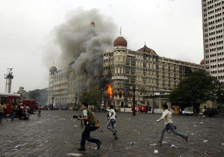 Photographers run past a burning Taj Mahal Hotel during a gun battle in Mumbai