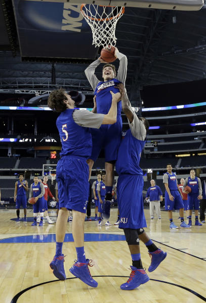Kansas' Tyler Self dunks with the help of Christophe Varidel (5) and Jamari Traylor during practice for a regional semifinal game in the NCAA college basketball tournament, Thursday, March 28, 2013, in Arlington, Texas. Kansas faces Michigan on Friday. (AP Photo/David J. Phillip)