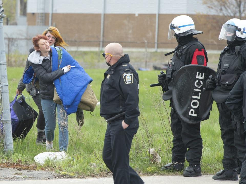 """<span class=""""caption"""">Police clear a homeless camp in Montréal's east end May 3, 2021. </span> <span class=""""attribution""""><span class=""""source"""">THE CANADIAN PRESS/Ryan Remiorz</span></span>"""