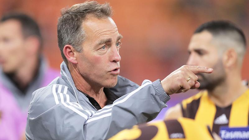 Pictured here, Hawthorn coach Alastair Clarkson addresses his players during an AFL game.