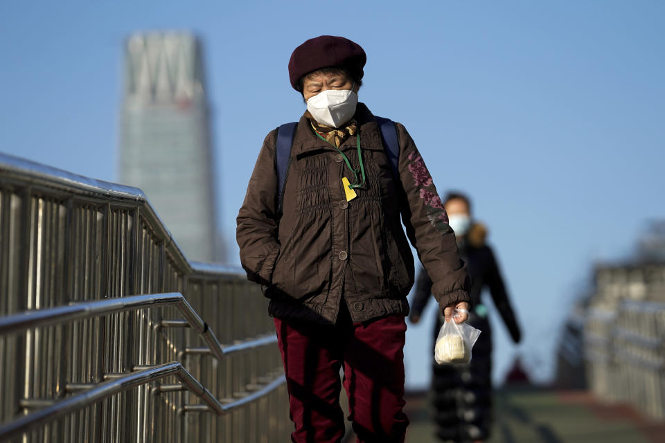 Women wearing face masks to help curb the spread of the coronavirus walk along a pedestrian bridge in Beijing, Monday, Nov. 30, 2020. (AP Photo/Andy Wong)