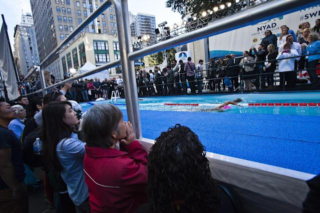 Pedestrians watch U.S. long-distance swimmer Diana Nyad during her 48 hour continuous swim at Herald Square in New York October 8, 2013. According to a media release, Nyad is holding the 48 hour continuous swim to support Hurricane Sandy recovery efforts. REUTERS/Eduardo Munoz (UNITED STATES - Tags: SPORT DISASTER SWIMMING)