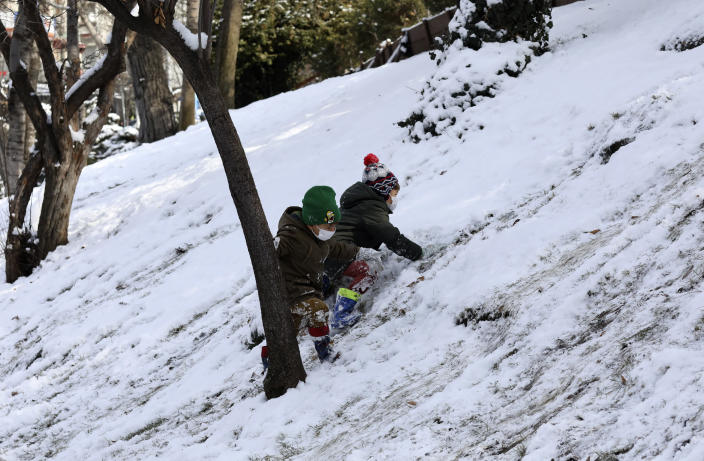 Children play at the snow-covered Kugulu Park public garden, in Ankara, Turkey, Monday, Jan. 18, 2021. Winter storms and snowfalls remains in effect for a large swath of Turkey, causing road accidents and closure of roads between cities and villages in many regions, hours after the snow falls blanketed the country. (AP Photo/Burhan Ozbilici)