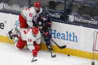 Detroit Red Wings' Luke Glendening, left, and Filip Hronek, front, fight for the puck against Columbus Blue Jackets' Oliver Bjorkstrand during the second period of an NHL hockey game Tuesday, March 2, 2021, in Columbus, Ohio. (AP Photo/Jay LaPrete)